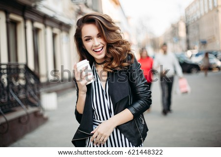 Happy brunette woman smiling at camera, drinking coffee at street and walking at spring season.Fashionable beautiful girl in black leather jacket,striped suite after beauty salon with perfect make up.