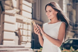 Happy brunette woman typing sms on smartphone in city