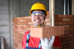 Happy builder holds brick for masonry and smiles. Red brick masonry. Calculation amount necessary building materials. Developer is building residential houses. Brick is used to lay foundation
