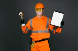 Happy builder worker holding in hands a golden cup award trophy and blank certificate isolated on black background.