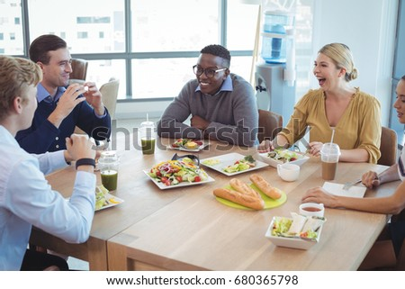 Happy business colleagues having lunch on table at office cafeteria