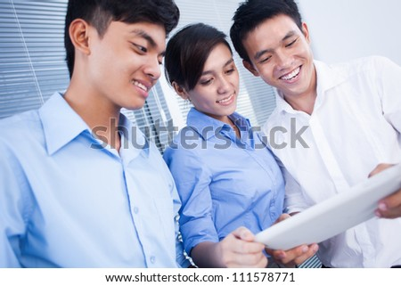 Happy business colleagues looking something on digital tablet