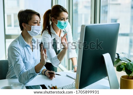 Happy business colleagues with face masks using computer and waving to someone during video call in the office.