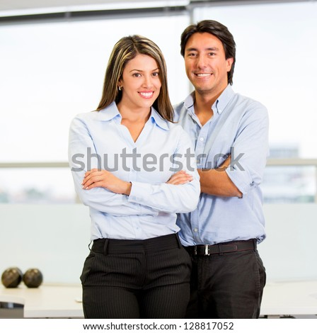 Happy business couple with arms crossed at the office