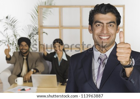 Happy business executives showing thumbs up sign