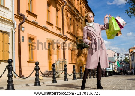 Happy, business girl who holds in hand bags, shopping. Consumerism, shopping, lifestyle concept. City landscape, Minsk, Belarus, September 2018 #1198106923