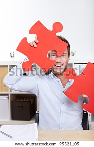 Happy business man cheering with oversized jigsaw puzzle pieces in office