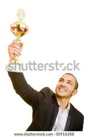 Happy business man holding a trophy aloft