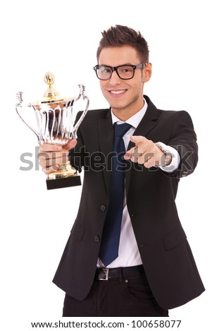 Happy business man holding a trophy and pointing to you over white background