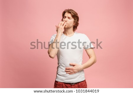 Happy business man licking fingers isolated on trendy pink studio background. Beautiful male half-length portrait. Young satisfy man. Human emotions, facial expression concept. Front view.