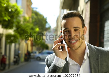 Happy business man making calls with smartphone in city