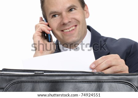 Happy business man on cell phone as he holds business letter from briefcase