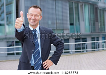 Happy business man outside holding his thumbs up