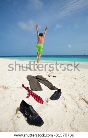 Happy business man running in to ocean to swim with clothes such as boots, tie and pants taken off and laying on the white sand