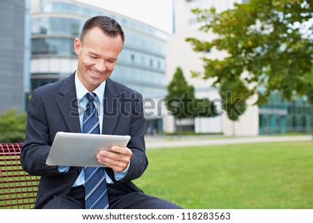 Happy business man using tablet PC outside on a park bench