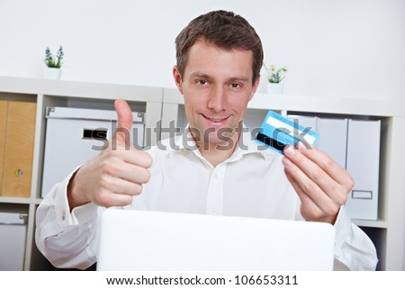 Happy business man with credit card holding thumbs up in the office