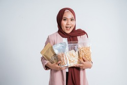 Happy business muslim woman portrait bring the snacks in small bag on white background