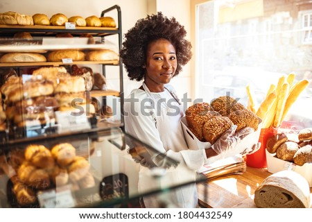 Happy business owner at a bakery shop. Young bakery owner holding a tray with bread in her shop. Beautiful baker. Happy woman working at the bakery and looking at the camera smiling - small business