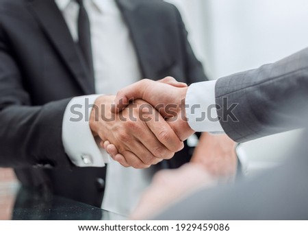 happy business partners shaking hands at the negotiating table.
