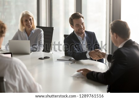 Happy business partners shaking hands expressing respect, closing banking investment corporate deal, welcoming at office group meeting, handshake of smiling businessmen as collaboration concept