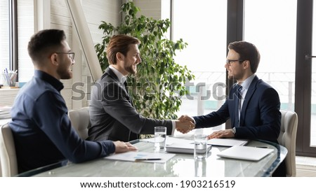 Happy business partners shaking hands, greeting or making successful great commercial deal after successful negotiations, smiling diverse employees sitting at table in modern boardroom, acquaintance