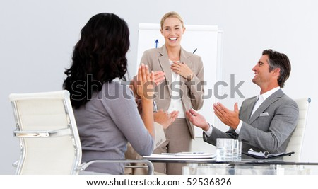 Happy business people applauding a good presentation in the office
