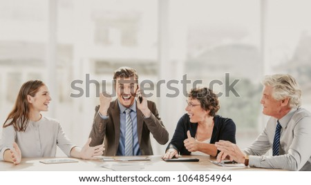 Happy business people being excited at new agreement. Young businessman talking on phone and showing yes gesture. His colleagues celebrating winning. They sitting at table. Success or teamwork concept #1064854964