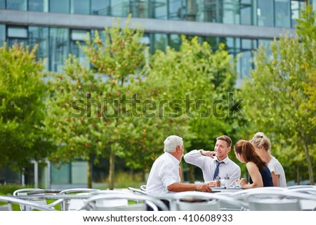 Happy business people in a coffee shop talking to each other outdoors