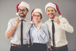 Happy business people in Santa hats are holding party props on sticks, looking at camera and smiling, on gray background