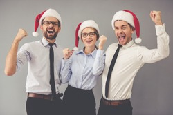 Happy business people in Santa hats are looking at camera and smiling while celebrating New Year, on gray background