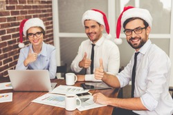 Happy business people in Santa hats are showing Ok sign and smiling while celebrating New Year in office