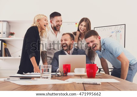 Happy business people laugh near laptop in the office. Successful corporate team of female and male coworkers joke and have fun together at work