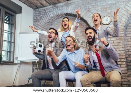 Happy business people or football fans watching soccer on tv and celebrating victory. Friendship, sports and entertainment concept.