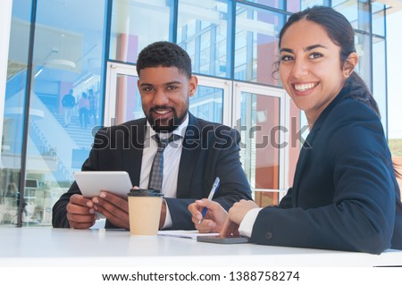 Happy business people posing and working in outdoor cafe. Business man and woman wearing formal clothes and sitting with building glass wall in background. Business people concept.