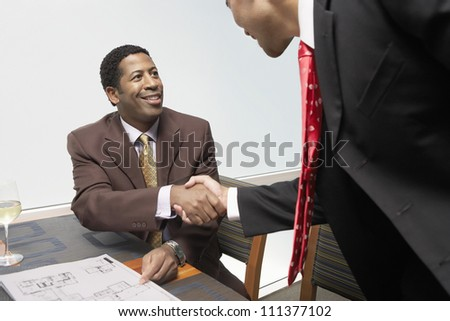 Happy business people shaking hands at office