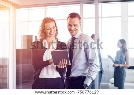 Happy business people working on tablet in modern office. Smiling businesswoman showing changes made in presentation. Happy businessman and business woman using tablet in office.