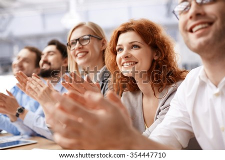 Happy business team applauding at conference
