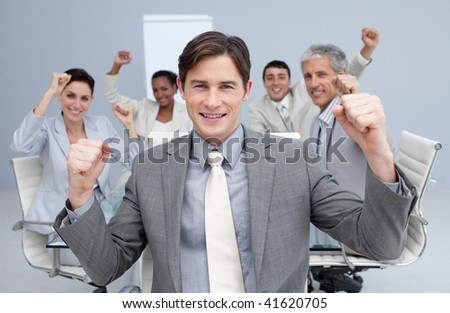 Happy business team celebrating a sucess with hands up in the office