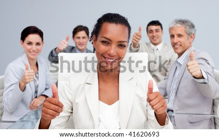 Happy business team celebrating a sucess with thumbs up in the office