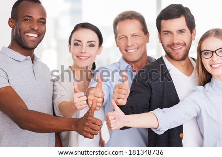 Happy business team. Group of cheerful business people in casual wear standing close to each other and showing their thumbs up