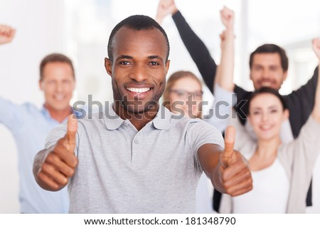 Happy business team. Happy young African man showing his thumbs up you and smiling while group of people in casual wear standing on background