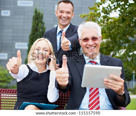 Happy business team holding their thumbs up with tablet computer in a park