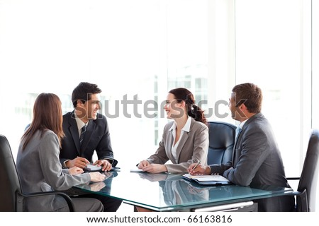 Happy business team talking together during a meeting sitting at a table