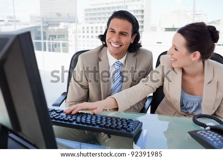 Happy business team using a computer in an office