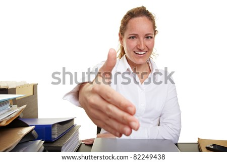 Happy business woman at desk offering welcome handshake