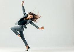 Happy business woman dancing and smiling in motion isolated over white studio background. Human emotions concept.  The businesswoman, office, success, elegance, grace, performer, flexible concepts
