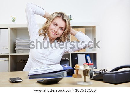 Happy business woman doing back exercises at work in her office