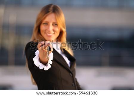 Happy Business woman hand holding key. Focus on keys - stock photo