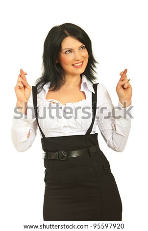 Happy business woman holding her fingers crossed looking away and wishing something isolated on white background