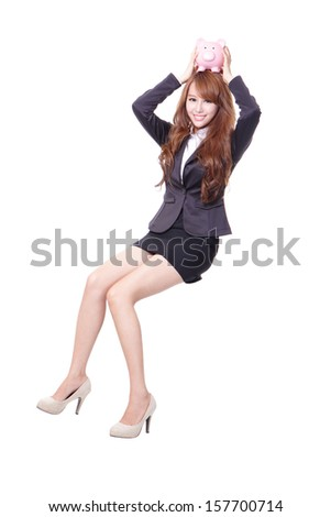 Happy business woman holding pink piggy bank and sitting on something isolated against white background, asian male model